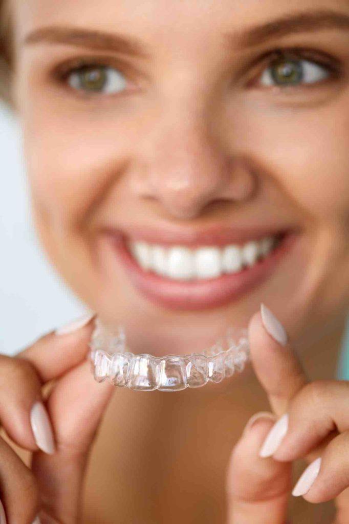 Frau hat unsichtbare Zahnspange in der Hand