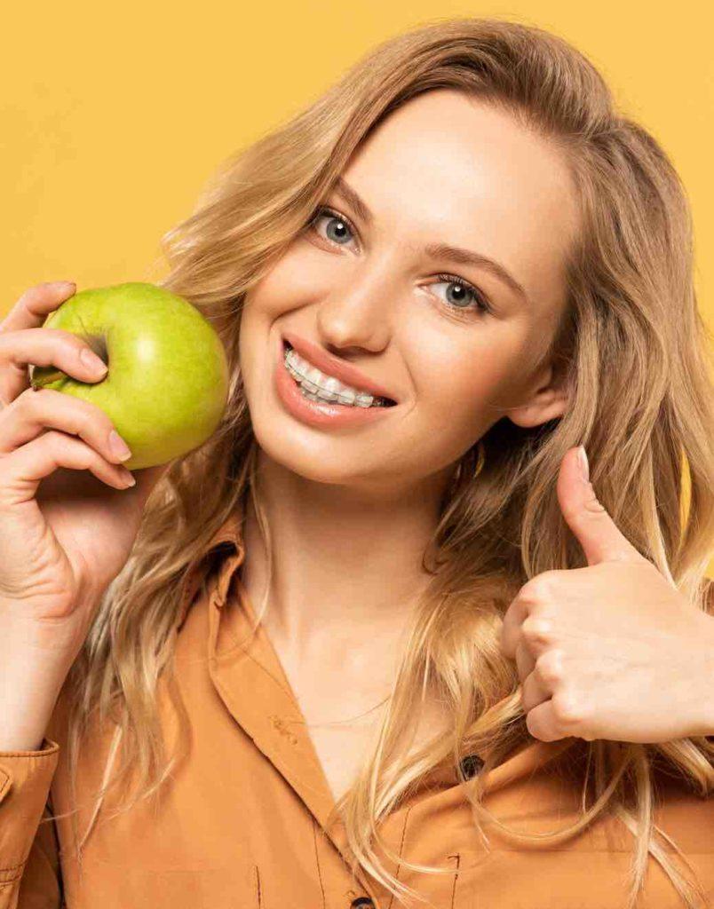 Kind mit Zahnspange hat Apfel in der Hand