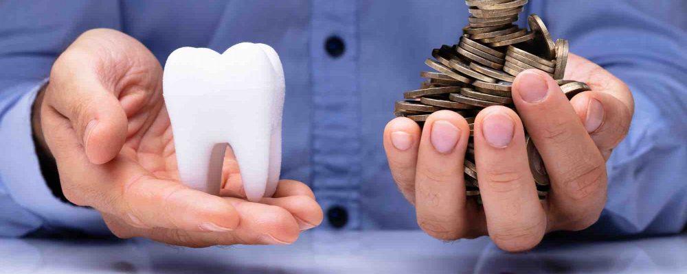 Mann hat Zahnmodell und Münzen in der Hand