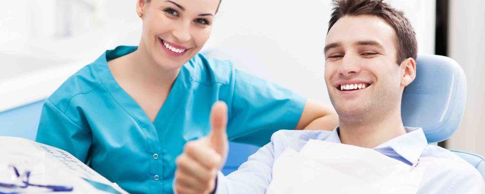 Patient sitzt neben Zahnarzt und hält Daumen hoch