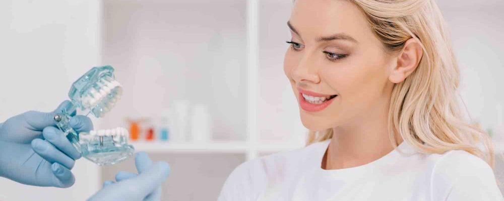 Kieferorthopäde erklärt Patient wie eine Zahnspange funktioniert
