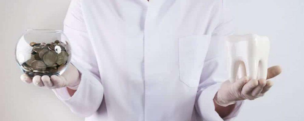 Kieferorthopäde hat Geld und Zahnmodell in der Hand